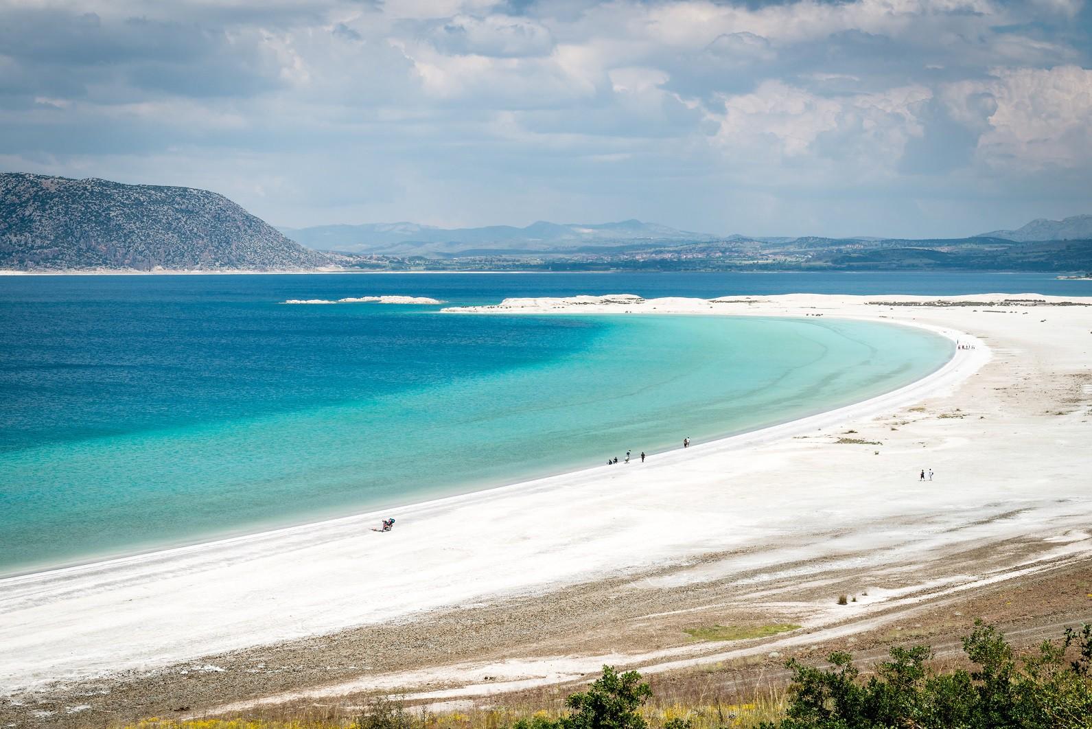SALDA GÖLÜ'NE İLGİ ARTIYOR Bembeyaz kumları ve masmavi sularıyla tropik bir adayı anımsatan Salda Gölü, son yıllarda seyahat severlerin en çok tercih ettikleri rotaların başında geliyor. Sit alanı olması nedeniyle bakir kalan ve adeta saklı bir cennet olan Salda, Denizli ve Antalya'nın ortasında konumlanıyor. (Fotoğraf: Salda)