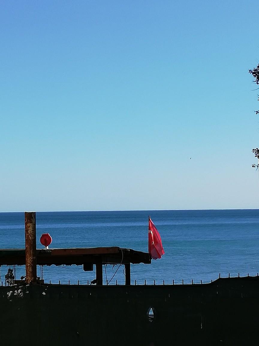 Gökyüzünün mavisi ile denizin laciverdi buluşuyor ve istisnasız her duvarda ay yıldızlı bir Türk bayrağı salınıyor.
