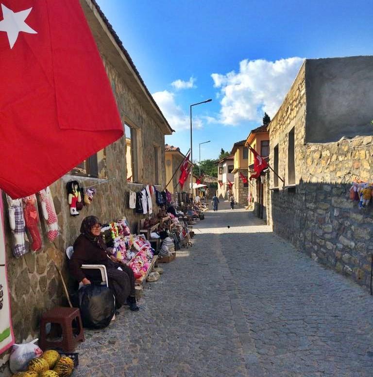 DUVAR BOYU EL İŞİ TEZGAHLARI SIRALI Kahvenin karşısında yerel ürünler satan köylü teyzeler sıra sıra dizilmiş. Arkamızda ise dev bir Atatürk posteri asılı. Orada durmuş sanki köye gelenleri karşılıyor.